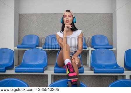 Dark-haired Girl In Roller-skates Listening To Music And Looking Thoughtful