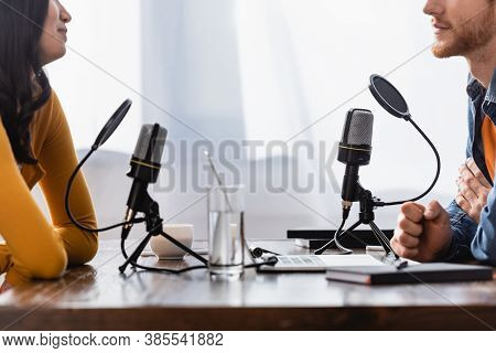Partial View Of Young Woman And Interviewer Near Microphones In Radio Studio