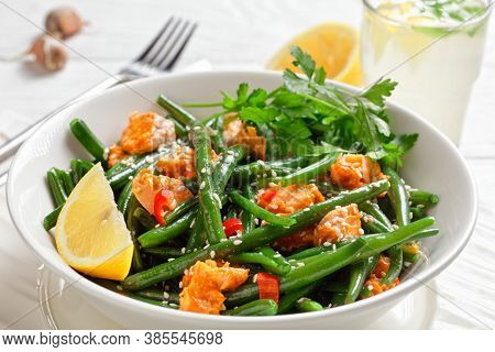 Curried Salmon With Green Beans, Red Bell Peppers Sprinkled With Sesame Seeds Served On A White Plat