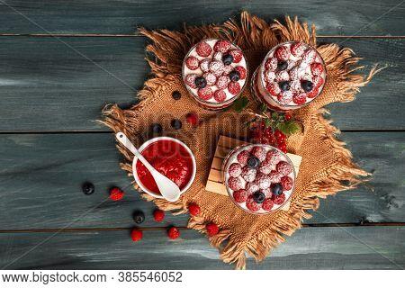 Healthy Raspberry Fruit Dessert With Skyr Yogurt, Granola Layered In Jar Surrounded By Ingredients,
