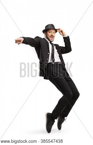 Full length shot of a man in a suit and hat dancing on tiptoes and pointing isolated on white background