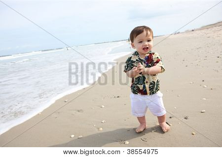A cute young baby boy playing in the sand at the beach