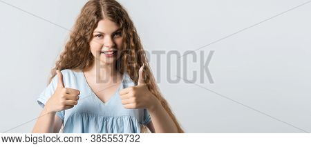 Attractive Calm Young Woman With Curly Long Hairstyle Shows Okay Sign With Both Hands, Demonstrates