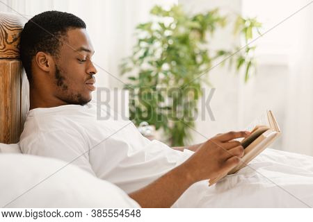Black Guy Reading Book Lying In Comfortable Bed In Bedroom At Home. African American Man Enjoying Lo