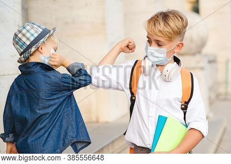Children With Face Mask Going Back To School. New Greeting Style. Kids Bumping Elbows Outdoors. Soci