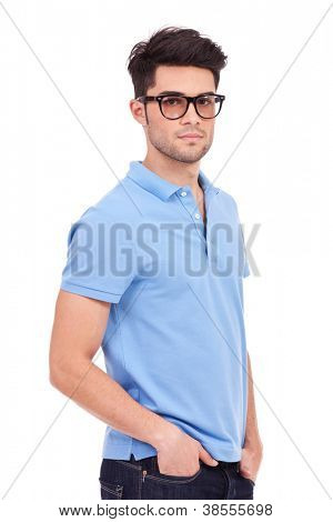 Angle view of a casual sexy young man holding his hands in his pockets and looking seriously at the camera