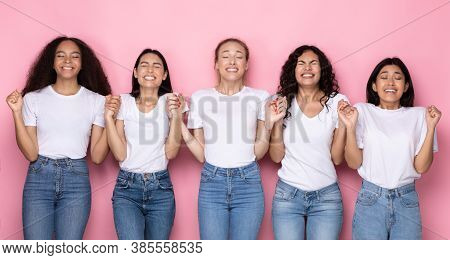 Group Of Multiethnic Women Making Wish Holding Hands Standing Together With Eyes Closed Over Pink Ba