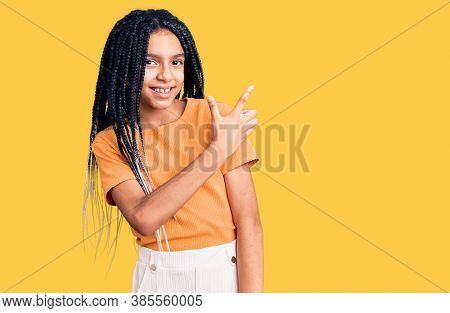 Cute african american girl wearing casual clothes cheerful with a smile of face pointing with hand and finger up to the side with happy and natural expression on face