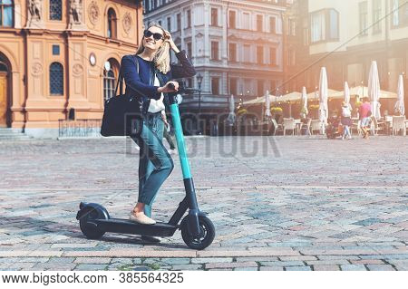 Millennial Woman Rides Electric Scooter In The City Streets. Eco Friendly Transportation