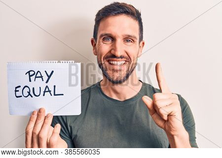 Young handsome man asking for equality economy holding paper with pay equal message smiling with an idea or question pointing finger with happy face, number one