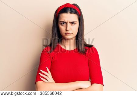 Young beautiful girl wearing casual t shirt and diadem skeptic and nervous, disapproving expression on face with crossed arms. negative person.