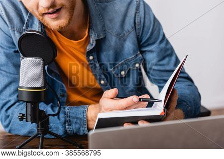 Partial View Of Bearded Broadcaster In Denim Shirt Holding Notebook And Pen While Speaking In Microp