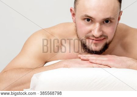 Young Caucasian Man Lying On Front On Table Spa, Waiting For Beauty Treatment And Looking At Camera