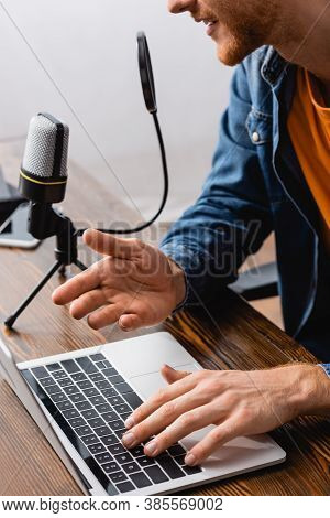 Partial View Of Broadcaster Talking In Microphone And Gesturing While Using Laptop At Workplace