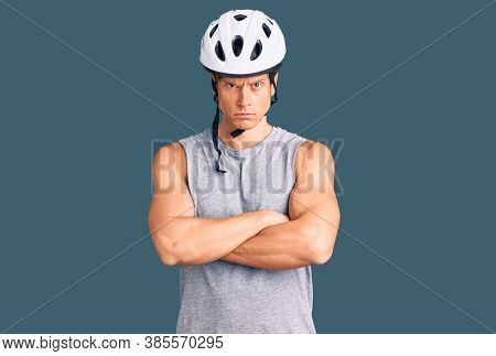 Young handsome man wearing bike helmet skeptic and nervous, disapproving expression on face with crossed arms. negative person.