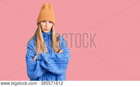 Beautiful caucasian woman with blonde hair wearing wool sweater and winter hat skeptic and nervous, disapproving expression on face with crossed arms. negative person.