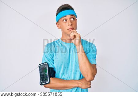 Young hispanic boy wearing sportswear thinking concentrated about doubt with finger on chin and looking up wondering