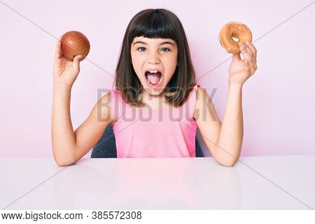 Young little girl with bang holding red apple and donut sitting on the table afraid and shocked with surprise and amazed expression, fear and excited face.