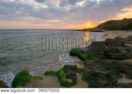 Sunrise At The Black Sea. Wonderful Calm Landscape With Rocks On The Beach Beneath A Cloudy Sky. Vel
