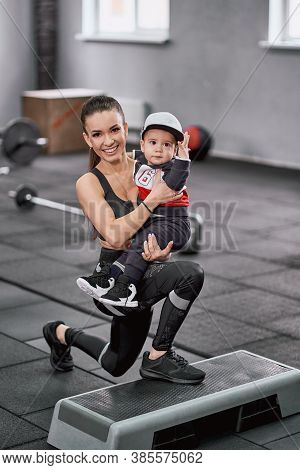 Portrait Of A Happy Mother With Her Little Child Doing Lunges Together