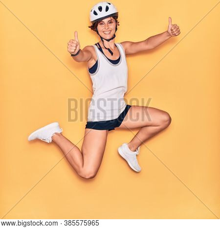 Young beautiful biker woman wearing bike helmet smiling happy. Jumping with smile on face doing ok sign with thumbs up over isolated yellow background.
