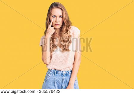 Young beautiful caucasian woman with blond hair wearing casual clothes pointing to the eye watching you gesture, suspicious expression