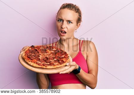Beautiful caucasian woman holding italian pizza in shock face, looking skeptical and sarcastic, surprised with open mouth