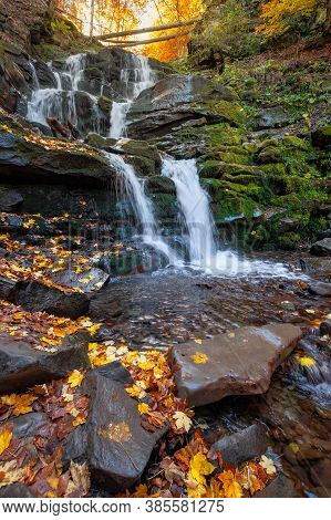 Waterfall In The Autumn Forest. Trees In Colorful Foliage. Water Runs Among The Rocks. Fallen Leaves