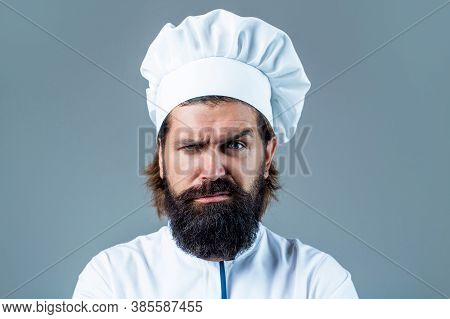 Confident Bearded Male Chef In White Uniform. Serious Cook In White Uniform, Chef Hat. Portrait Of A