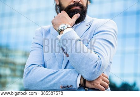 Watch In A Man. Businessman Points To His Watch On The Background Of The Town. The Man Holds His Wat