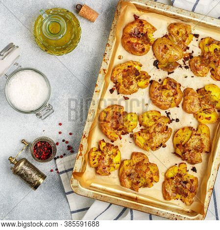 Oven Baked Whole Crushed And Crusty Potato With Coarse Sea Salt, Olive Oil, Garlic, Pepper And Thyme