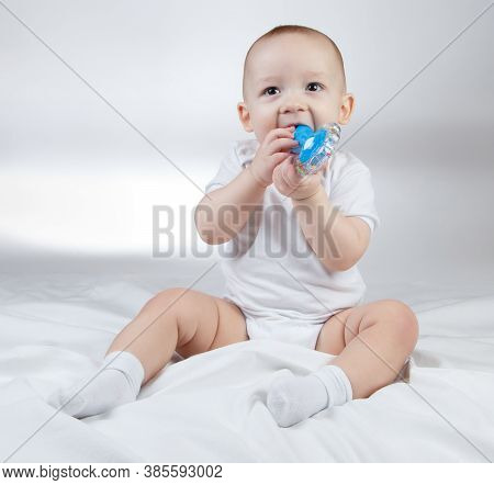 Photo Of A Ten-month-old Baby With Blue Rattle