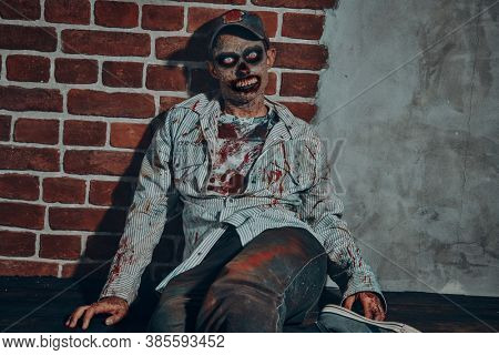 Scary bloodthirsty zombie man in a ruined building. Horror. Halloween. Portrait in red light.