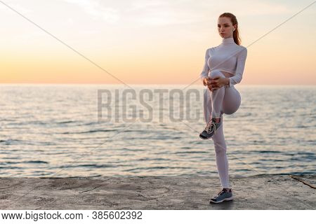 Image of redhead focused girl in earphones doing exercise while working out on promenade at sunrise