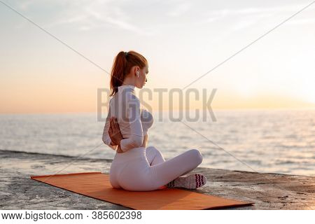 Image of redhead calm girl in earphones doing yoga exercise on promenade at sunrise