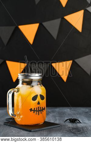 Iced Pumpkin Cocktail In Glass Jar Decorated With Scary Face On A Dark Table. Diy Halloween Party De