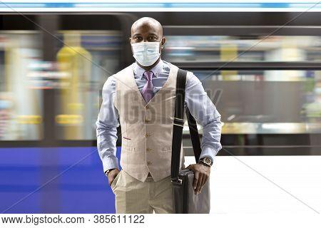 Enterprising Black Man Wearing A Face Mask Walking Near A Moving Subway Train. Safe Travel During Th