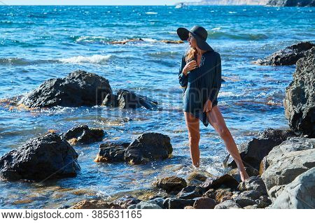 Summer Vacation. Smiling And Happy Woman In Hat. Rocky Coastline And Blue Sea. Meditation And Moment