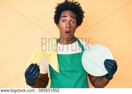 Handsome african american man with afro hair wearing apron holding scourer washing dishes in shock face, looking skeptical and sarcastic, surprised with open mouth