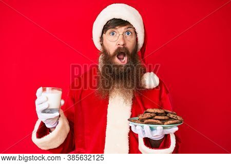 Handsome young red head man with long beard wearing santa claus costume holding cookies and milk in shock face, looking skeptical and sarcastic, surprised with open mouth
