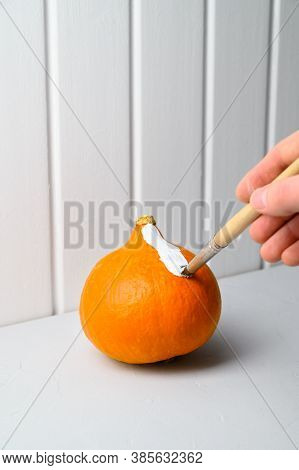Halloween Concept. A Male Hand With A Paintbrush Paints An Orange Pumpkin White On The Table. Vertic