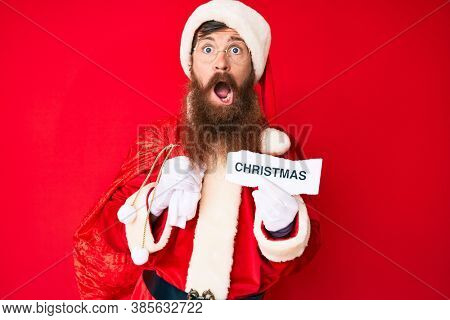 Handsome young red head man with long beard wearing santa claus costume holding christmas text in shock face, looking skeptical and sarcastic, surprised with open mouth