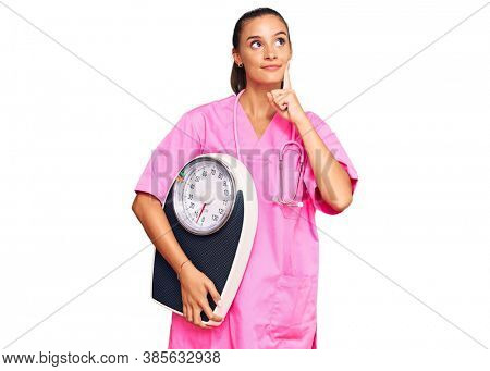Young hispanic woman as nutritionist doctor holding weighing machine serious face thinking about question with hand on chin, thoughtful about confusing idea