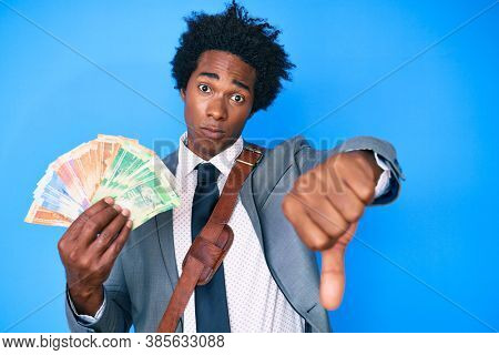Handsome african american man with afro hair holding south african rand banknotes with angry face, negative sign showing dislike with thumbs down, rejection concept