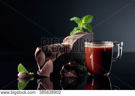 Chocolate And Mint. Pieces Of Dark Bitter Chocolate And Glass Cup With Hot Chocolate On A Black Refl
