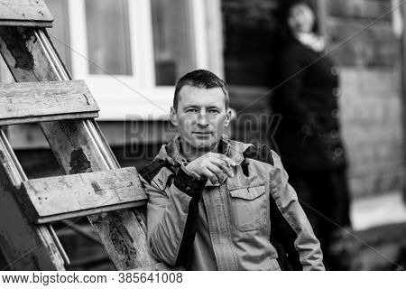 Portrait of man smokes a cigarette, standing outdoors. Black and white photography.