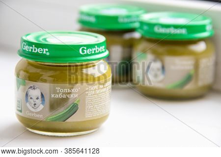 Moscow, Russia - September 12, 2020: Gerber Jars With Child Nutrition Vegetable Purre On Pattern Bac
