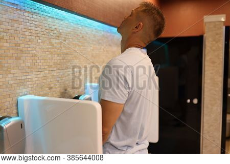 Man In White T-shirt Stand In Toilet And Look Up. Person Pissing Into Fashionable Urinal.