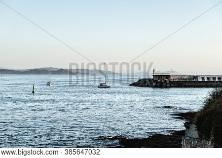 Small Boats Sailing Back To Port On A Calm Clear Evening In The Rias Baixas In Galicia, Spain.