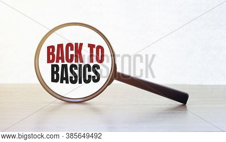 Magnifying Glass With Text Back To Basics On Wooden Table.